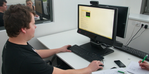 A person sitting in front of the Tobii Pro TX300 eye tracker in the UX lab.