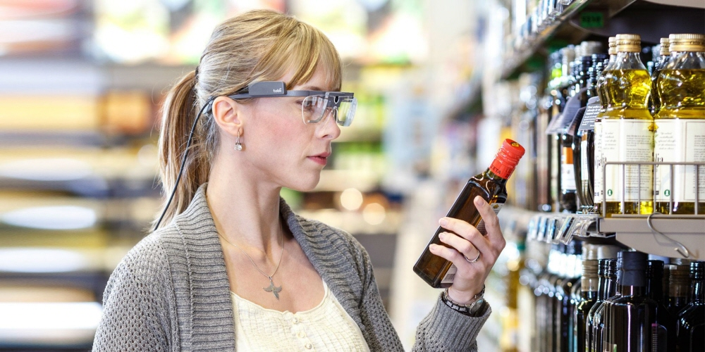 A woman wearing Tobii Pro Glasses 2 looks at an oil bottle.