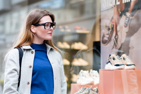 Woman looking at a store window wearing Tobii Pro Glasses 3