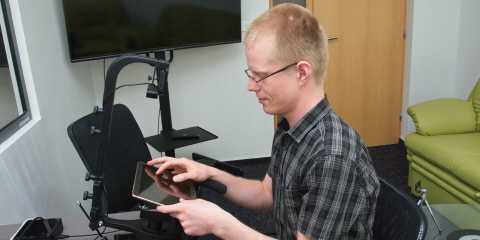 A person sitting in front of the Tobii Pro X2-60 eye tracker mounted on the desk stand.