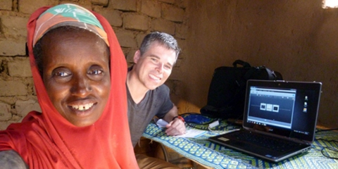 A woman performs an eye tracking test with Tobii Pro X2-60 in a traditional mud brick home.