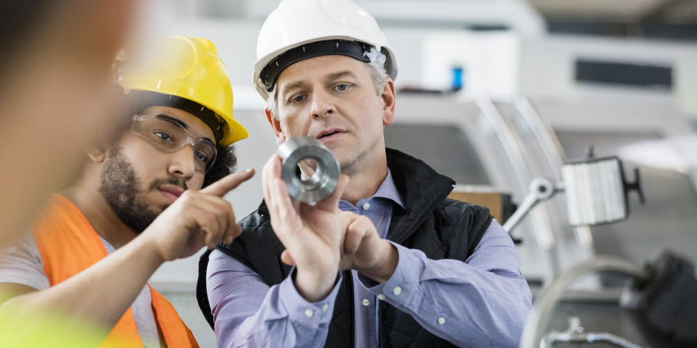 Men looking at a steel part - knowledge transfer