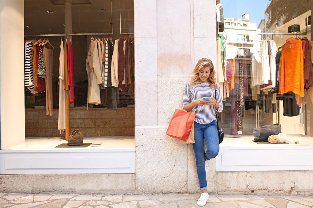 Woman standing in front of shops looking at her mobile phone.