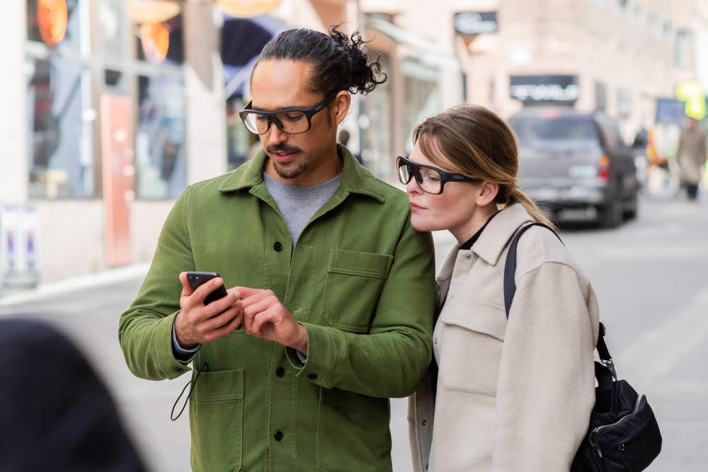 Two people using wearable eye trackers to look at a mobile phone