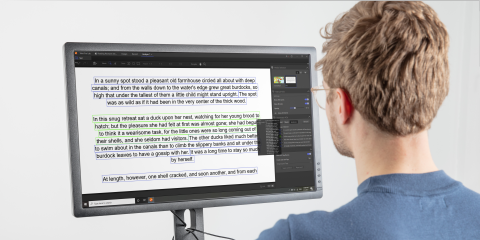 A man reading a text from a desktop screen